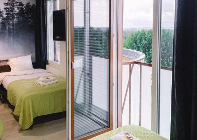 Hotelli huone jossa parvekkeen ovi auki